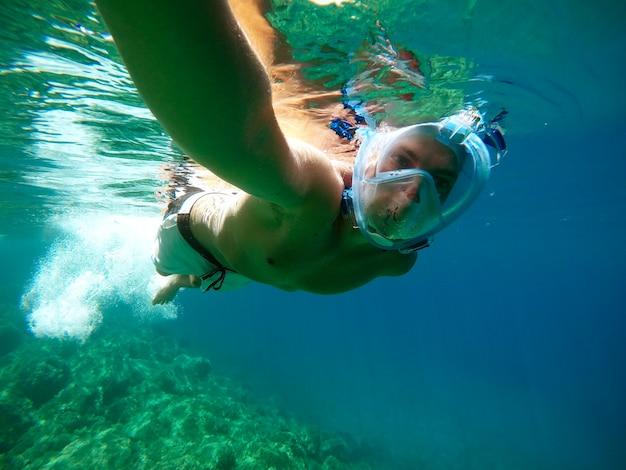 Podwodny widok młodego mężczyzny nurka pływającego w turkusowym morzu pod powierzchnią z maską do nurkowania na letnie wakacje podczas robienia selfie z kijem.