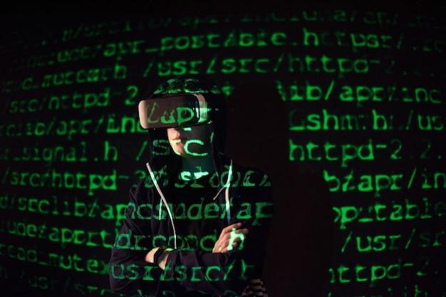 Podwójna ekspozycja kaukaskiego mężczyzny i zestawu słuchawkowego vr vr to prawdopodobnie gracz lub haker, który włamuje kod do bezpiecznej sieci lub serwera, z liniami kodu w kolorze zielonym