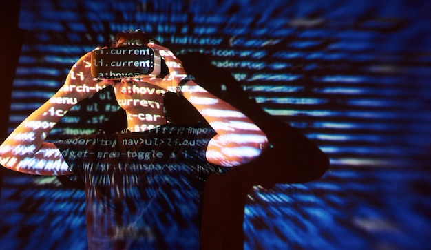 Podwójna ekspozycja mężczyzny rasy kaukaskiej i zestawu słuchawkowego vr vr to prawdopodobnie gracz lub haker, który włamuje kod do bezpiecznej sieci lub serwera za pomocą linii kodu