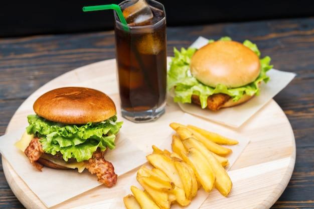Podwójna porcja dwóch burgerów z frytkami i dużą szklanką sody lub coli z lodem na okrągłej drewnianej desce oglądana pod dużym kątem