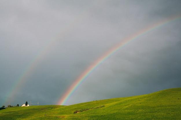 Podwójna tęcza na tle nieba i zielonych wzgórz