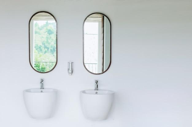 Podwójna umywalka na białej ścianie z dwoma lustrami