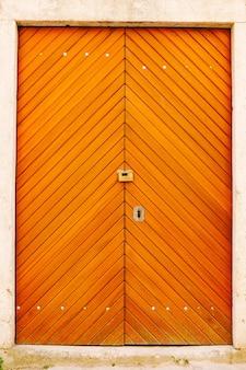 Podwójne drzwi w jasnopomarańczowe paski ze sprzętem