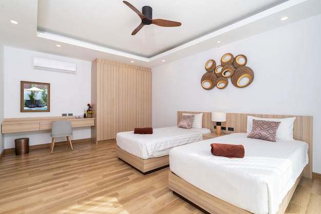 Podwójne łóżko w przestronnej sypialni z wentylatorem sufitowym, szafą i biurkiem