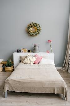 Podwójne łóżko z jasnymi poduszkami i dekorowaną sypialnią