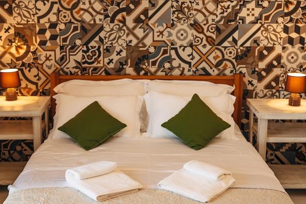 Podwójne łóżko z poduszkami i ręcznikami frotte między stolikami z lampkami nocnymi pod ścianą