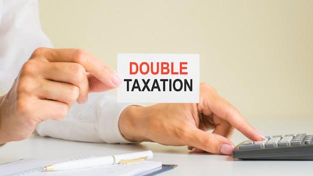 Podwójne opodatkowanie, wiadomość na wizytówce pokazana przez kobietę naciskającą klawisz kalkulatora w miejscu pracy w jasnym biurze, selektywne skupienie, koncepcja biznesowa i finansowa