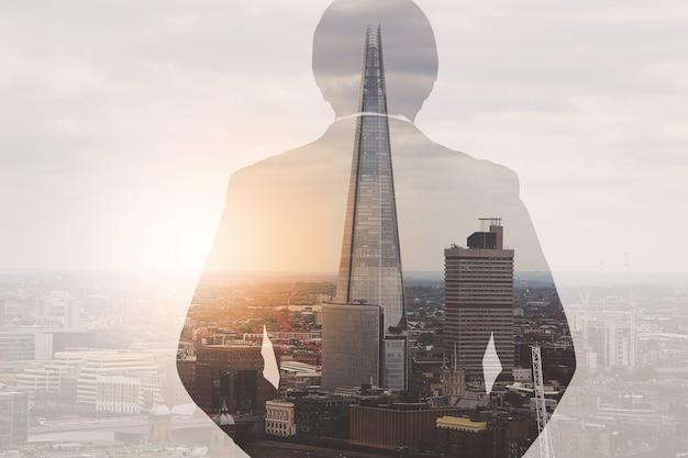 Podwójnej ekspozycji biznesmen sukcesu za pomocą inteligentnego telefonu z budynku w londynie, efekt filtra