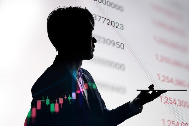 Podwójnej ekspozycji sylwetka biznesmen używać tabletu z cennikiem giełdowym. koncepcja dla biznesu i gospodarki finansowej.