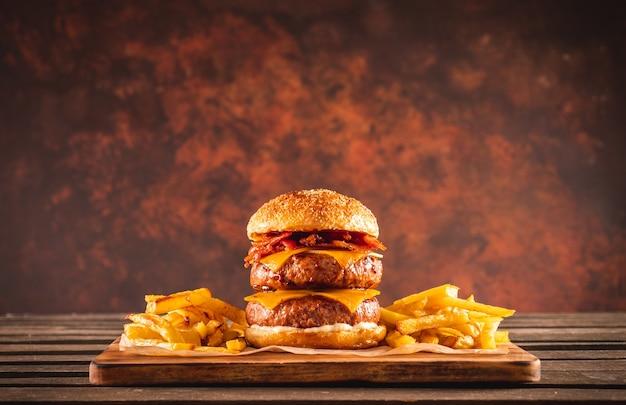 Podwójny burger wołowo-bekonowy z serem cheddar i frytkami na drewnianej desce