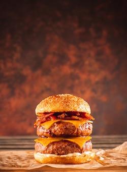 Podwójny burger wołowo-bekonowy z serem cheddar na drewnianym stole