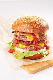 Podwójny cheeseburger na białym tle i drewniane biurko
