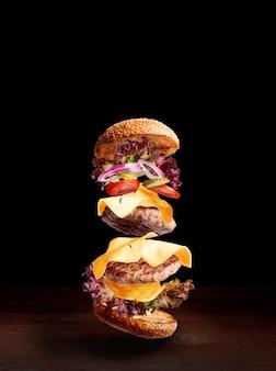 Podwójny cheeseburger na drewnianej powierzchni z ciemnym tłem i przestrzenią dla teksta