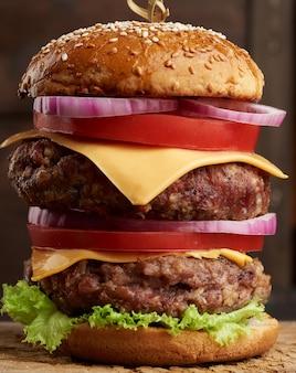 Podwójny cheeseburger z pomidorami, cebulą, kotletem barbecue i bułką sezamową na starej drewnianej desce do krojenia. fast food, z bliska