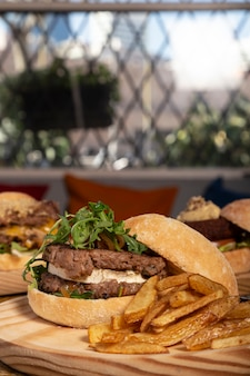 Podwójny domowy hamburger z kozim serem i frytkami na drewnianym stole. obraz pionowy