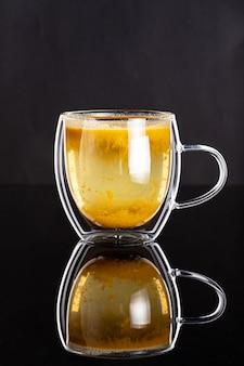 Podwójny szklany kubek z domową zdrową herbatą rokitnika na czarnej powierzchni