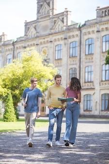 Podwórko uczelni. trzech studentów spacerujących po dziedzińcu uczelni i rozmawiających