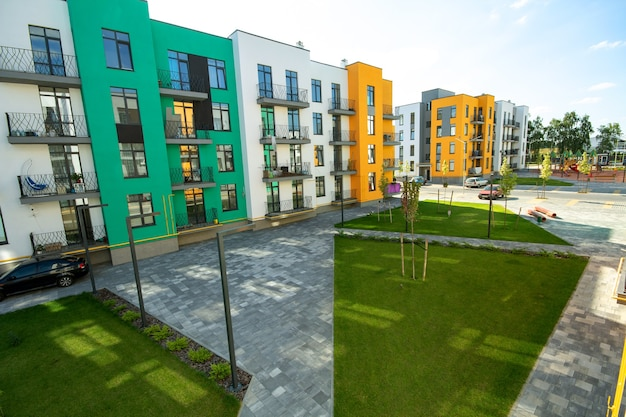 Podwórze pomiędzy apartamentowcami z trawnikami zielonymi i nowoczesnymi mieszkaniami. rozwój nieruchomości.