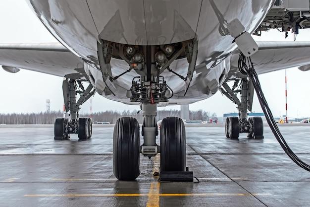 Podwozie i koła samolotu zaparkowane na lotnisku, z podstawowym zasilaniem.