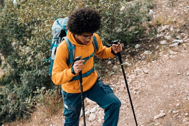 Podwyższony widok afrykańskiego młodego człowieka pieszego w górach