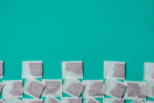 Podwyższony widok biała herbaciana torba na zielonym tle