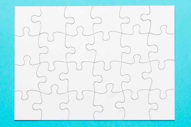 Podwyższony widok biała układanki puzzle na niebieskiej powierzchni