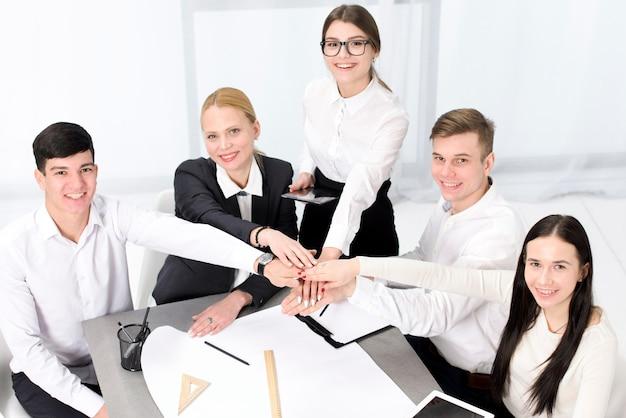 Podwyższony widok biznesmen i businesswoman układania nawzajem ręce nad projektem