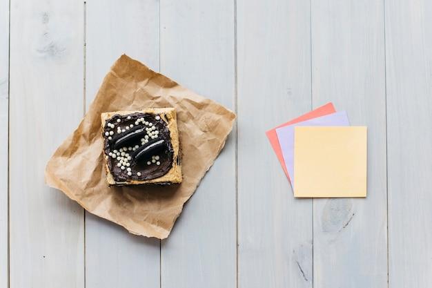 Podwyższony widok ciasto blisko kolorowych adhezyjnych notatek na drewnianym tle