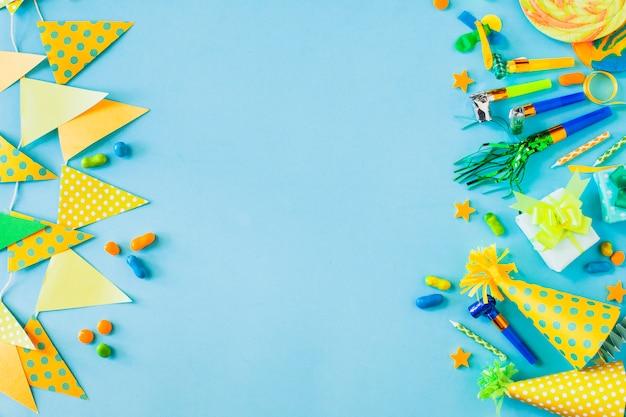 Podwyższony widok cukierki z partyjnymi akcesoriami na błękitnym tle