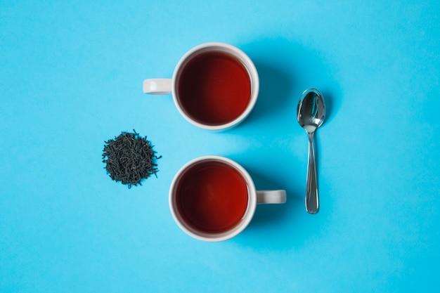 Podwyższony widok czarne ziołowe herbaciane filiżanki i łyżka na błękitnym tle