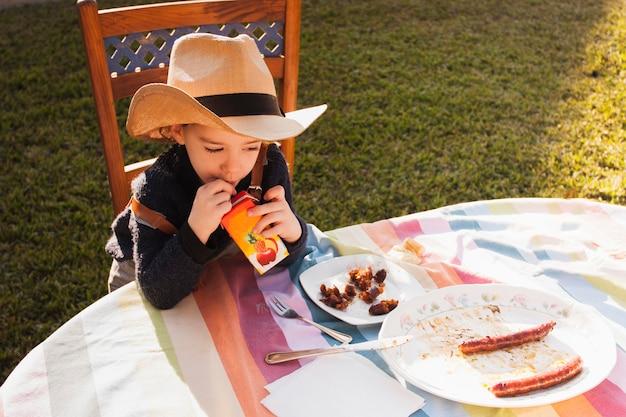 Podwyższony widok dziewczyna pije sok w kapeluszu