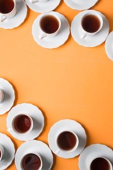 Podwyższony widok filiżanki herbaty ziołowe i spodki na rogu pomarańczowym tle