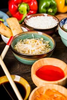 Podwyższony widok kiełków fasoli i miseczki sosu drewnianego biurka