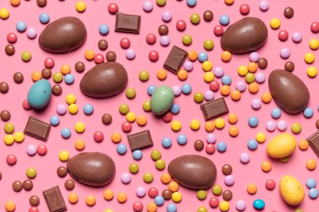 Podwyższony widok klejnotów cukierki i czekoladowe jaja wielkanocne na różowym tle