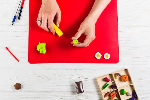 Podwyższony widok kobiety ręki mienia glina na stole