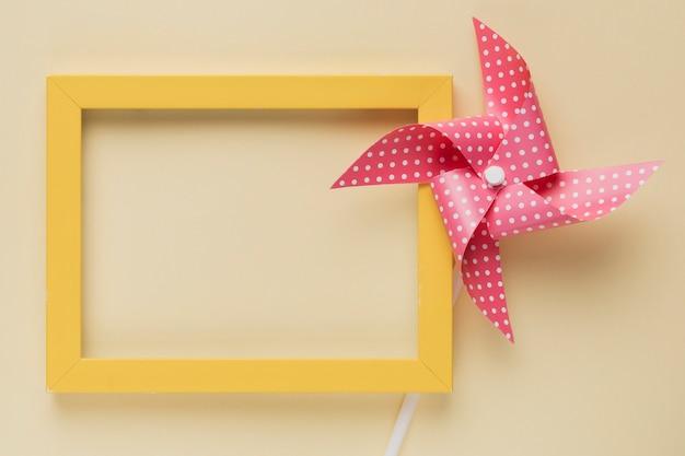 Podwyższony widok kropkowana pinwheel i kolor żółty rama na beżowym tle