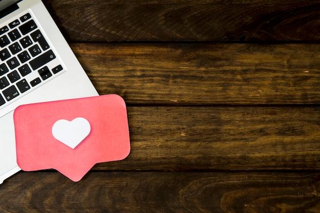 Podwyższony widok laptop i jak ikona na drewnianym stole