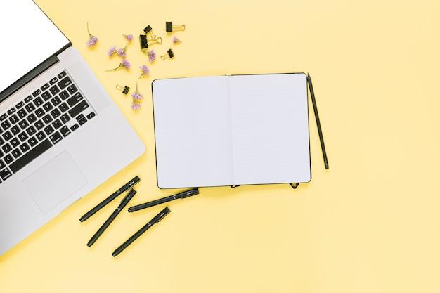 Podwyższony widok laptop z stationeries i kwiatami na żółtym tle