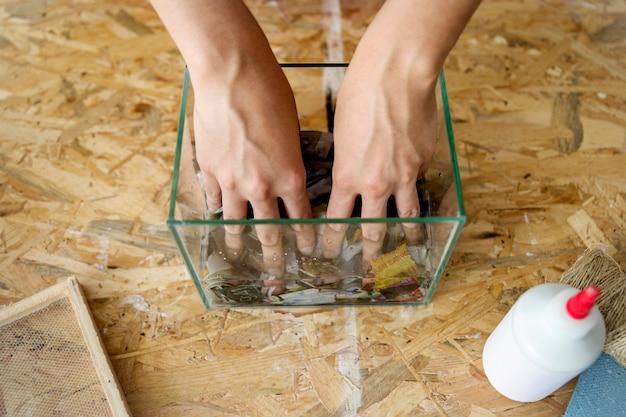 Podwyższony widok miesza papierowych kawałki w wodzie kobieta
