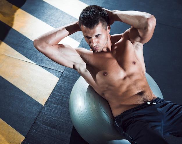Podwyższony widok młody człowiek ćwiczy na sprawności fizycznej piłce