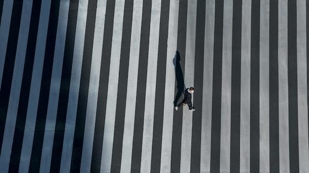 Podwyższony widok na mężczyznę na przejściu dla pieszych na skrzyżowaniu dróg w japonii. widok z lotu ptaka ludzi na przejściu dla pieszych. śródmieście azji. metropolitalne miasto tokio