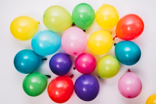 Podwyższony widok nadymający kolorowi balony na białym tle