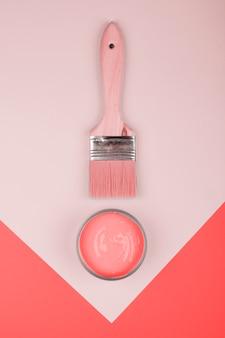 Podwyższony widok paintbrush i koralowa farba na geometrycznym papierowym tle