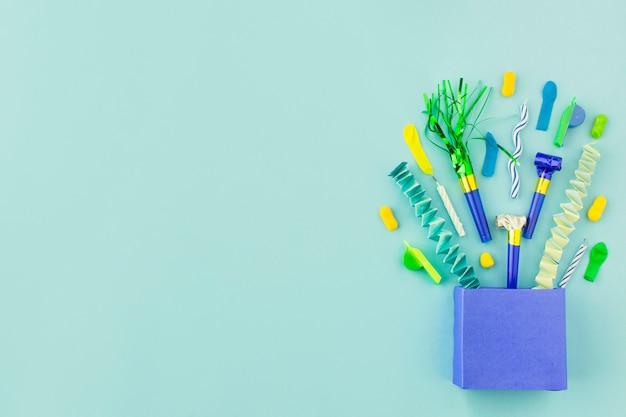 Podwyższony widok papierowa torba z urodzinowymi akcesoriami na zielonym tle