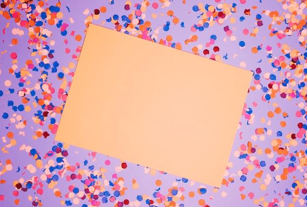 Podwyższony widok pusty papier nad kolorowymi confetti przeciw purpurowemu tłu