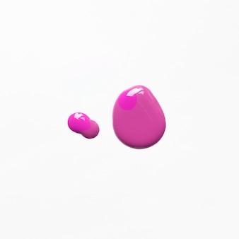 Podwyższony widok różowy gwoździa połysku upadek na białym tle