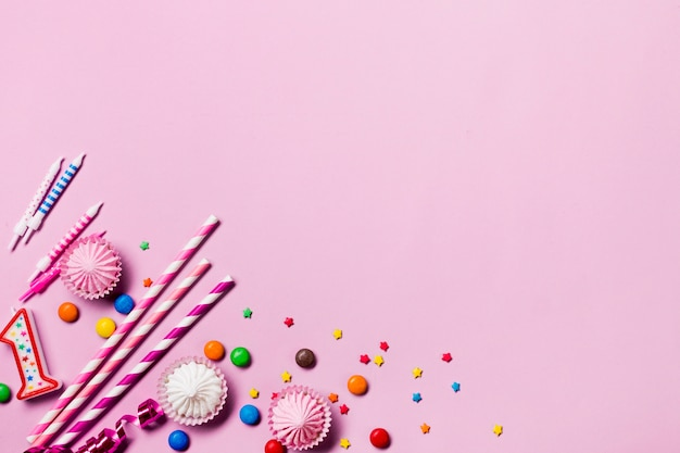 Podwyższony widok słomek do picia; świece; klejnoty; serpentyny i kropi na rogu różowego tła