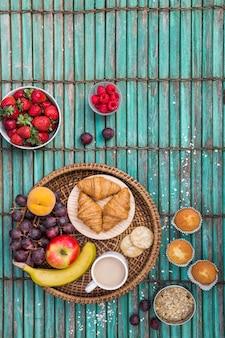 Podwyższony widok śniadanie na pasiastym drewnianym tle