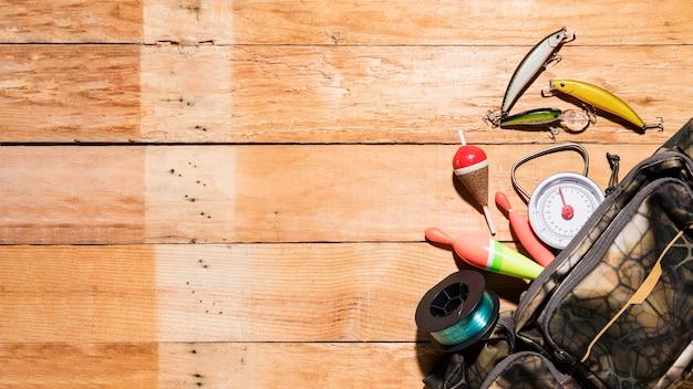 Podwyższony widok spławików rybackich; wabik; kołowrotek i miarka z worka na drewnianym biurku