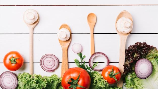 Podwyższony widok świezi warzywa z łyżkami na drewnianym tle